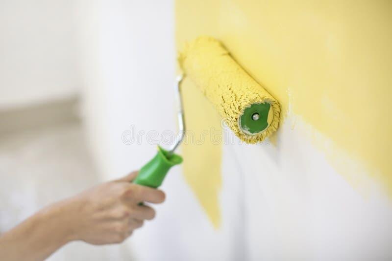 Parede masculina da pintura do decorador com rolo dentro imagens de stock royalty free