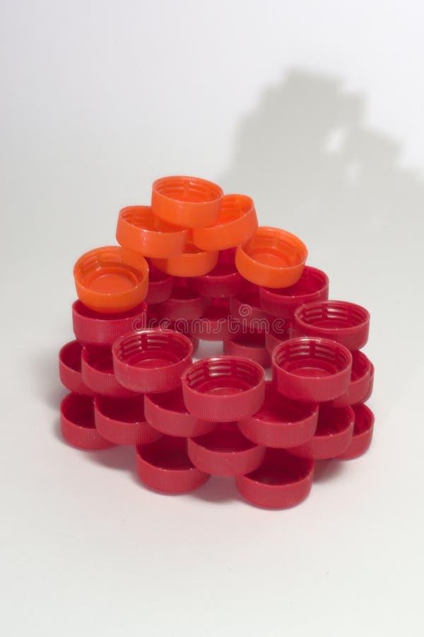 A parede pequena anular feita de tampões de garrafa plásticos multicoloridos moldou s fotos de stock