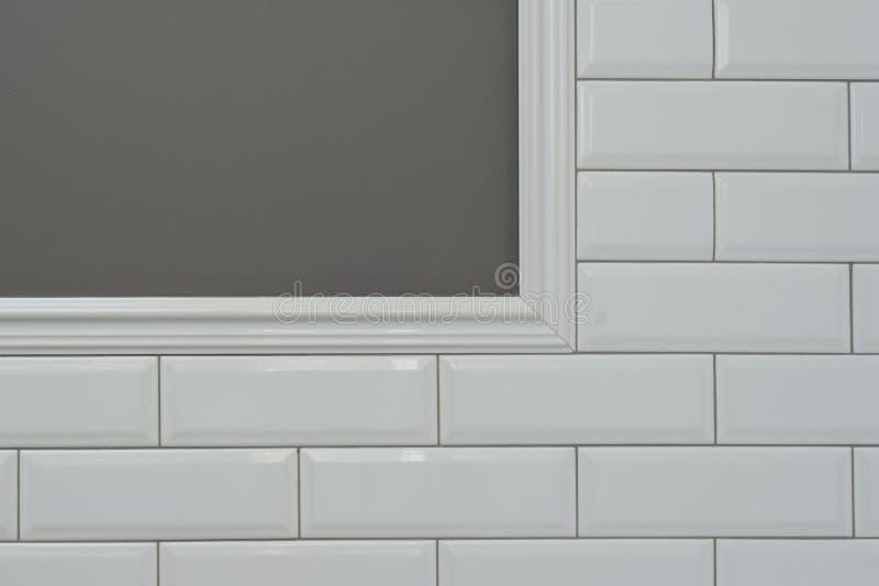 A parede pintada cinza, peça da parede é tijolo lustroso branco pequeno coberto das telhas, telhas decorativas cerâmicas do molde imagens de stock