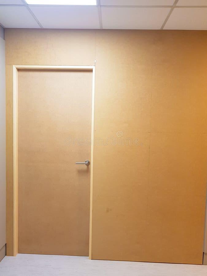 A parede pintou marrom com a porta de madeira igualmente marrom em um lado Ideia frontal do todo fotografia de stock royalty free