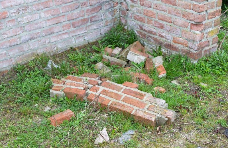 Parede quebrada, tijolos na terra fotos de stock