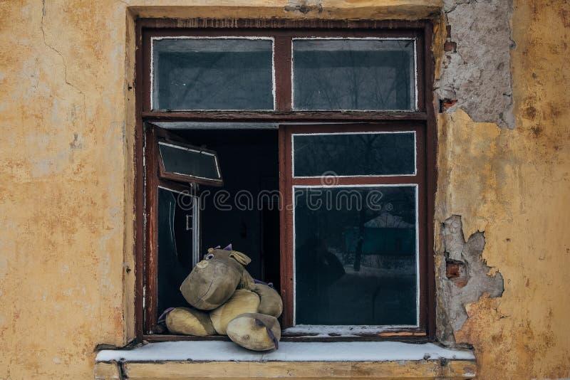 Parede rachada suja gasto, janela quebrada, dragão velho do brinquedo no conceito da soleira, do inverno, da pobreza e da tristez fotografia de stock royalty free