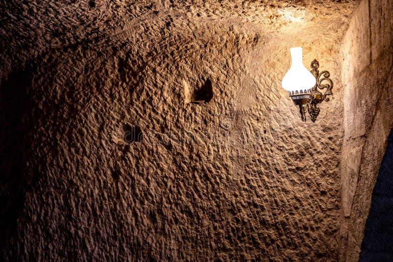 Parede ?spera antiga na caverna com luz da l?mpada na escurid?o imagens de stock royalty free
