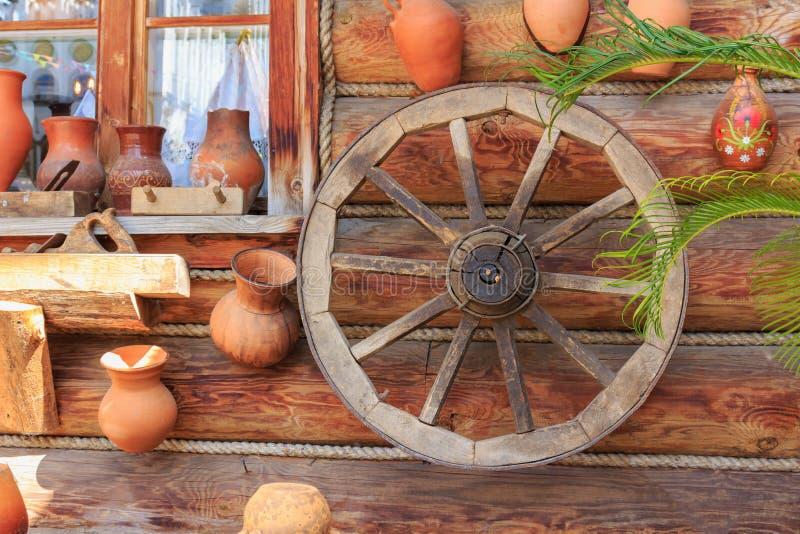 Parede suportada de uma casa da vila com jarros e cartwheel da argila no dia ensolarado foto de stock