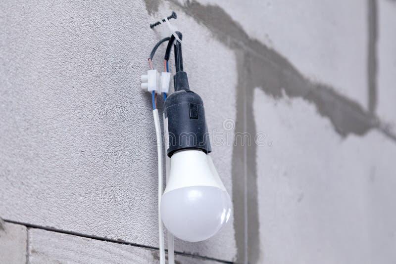 Parede textured do fundo do close up do concreto ventilado cinzento com os bulbos ásperos e dois elétricos no cair do cabo no pre fotos de stock