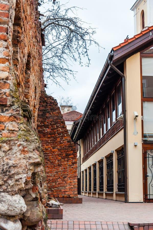 Parede velha arruinada medieval antiga da fortaleza da cidade perto da construção de escritórios para negócios europeia da arquit imagens de stock