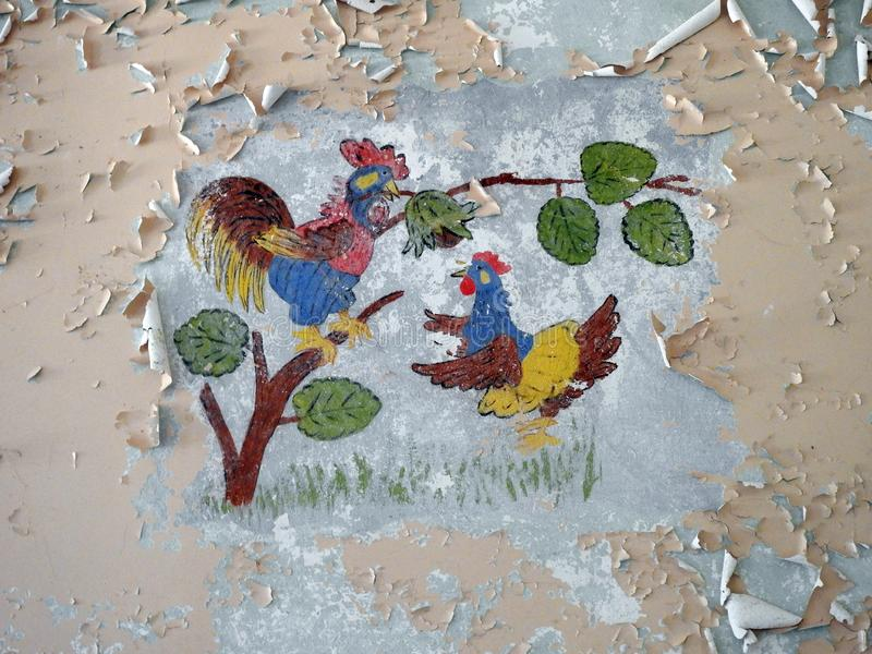 Parede velha com galinha e o galo pintados, Lituânia foto de stock