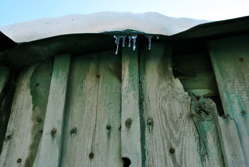 Parede velha de madeira verde, telhado com sincelos e neve branca na parte superior, vista da terra no fundo claro azul do céu imagens de stock