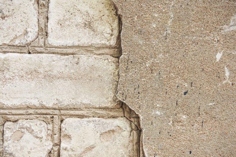 A parede velha do tijolo branco com um emplastro quebrado, rachado abstraia o fundo fotos de stock