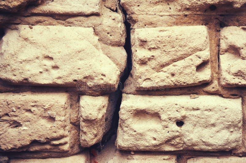 A parede velha do tijolo branco com um emplastro quebrado, rachado abstraia o fundo imagens de stock royalty free