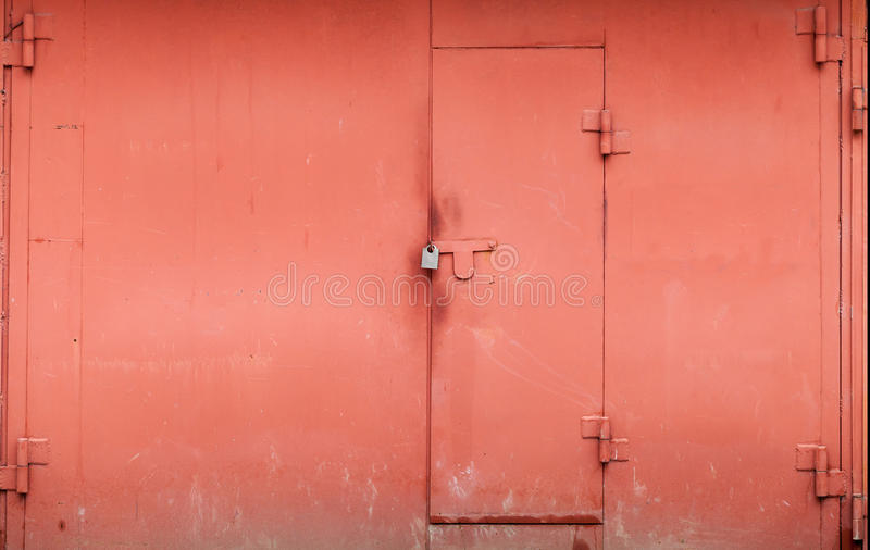 Parede vermelha da garagem do metal com porta fechado fotografia de stock
