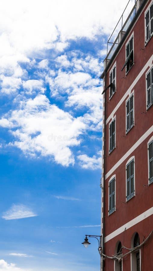 Parede vermelha velha da casa da lâmpada de rua contra o céu azul com nuvens brancas Italy Um bom lugar para caminhadas romântica imagem de stock royalty free