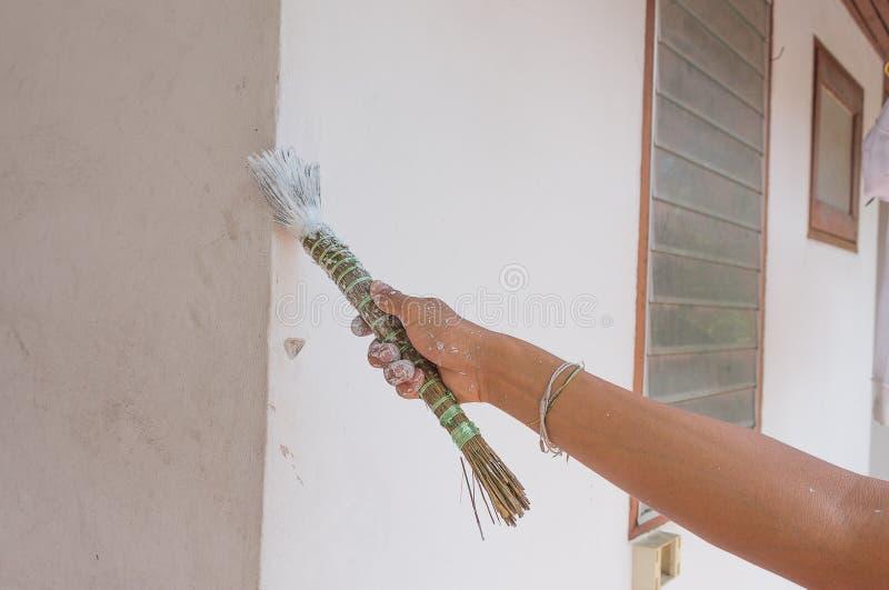 Paredes de la pintura Pinturas del pintor usando un cepillo, cepillo de la tenencia del trabajador de la mano que pinta blanco en fotografía de archivo libre de regalías