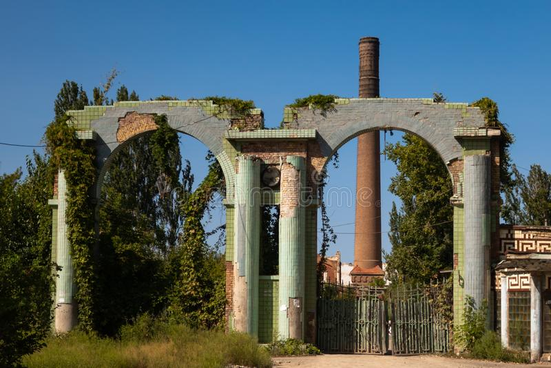 Paredes de ladrillo de una fábrica abandonada vieja con una chimenea Una fábrica abandonada con un alto tubo del ladrillo Entrada imagen de archivo