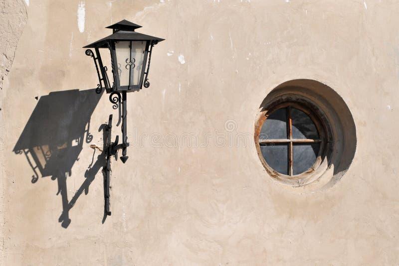 Paredes de uma casa velha com uma janela redonda e uma lanterna fotos de stock royalty free