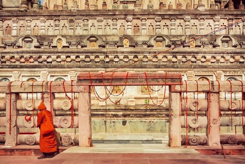 Paredes del templo histórico tallado de Budhist y del monje que camina solo en el vestido rojo amarillo cerca de la puerta, la In fotos de archivo libres de regalías