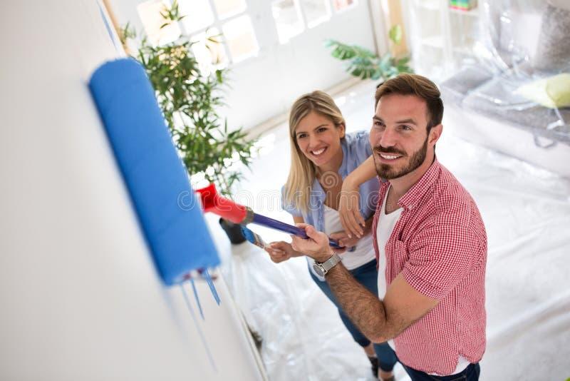Paredes felizes novas da pintura dos pares no apartamento novo fotografia de stock