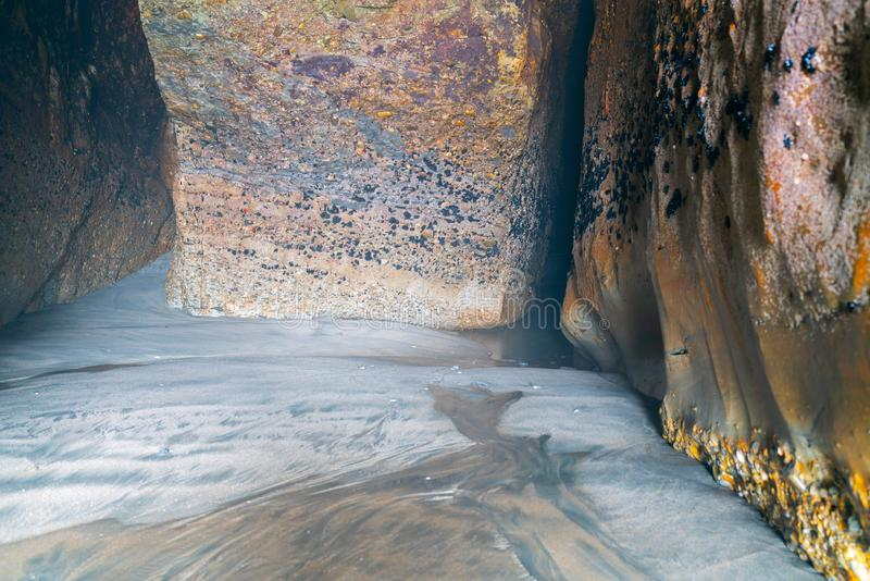 Paredes gastas envelhecidas do tempo e da caverna da rocha do mar foto de stock