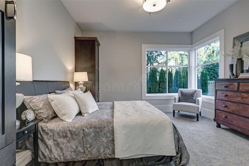 Paredes grises suaves de las características interiores acogedoras del dormitorio foto de archivo libre de regalías