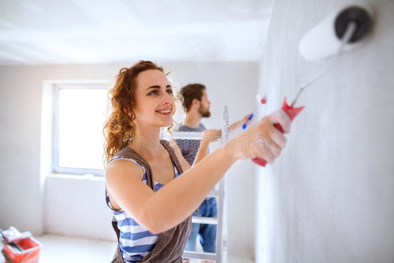 Paredes jovenes de la pintura de los pares en su nueva casa foto de archivo libre de regalías