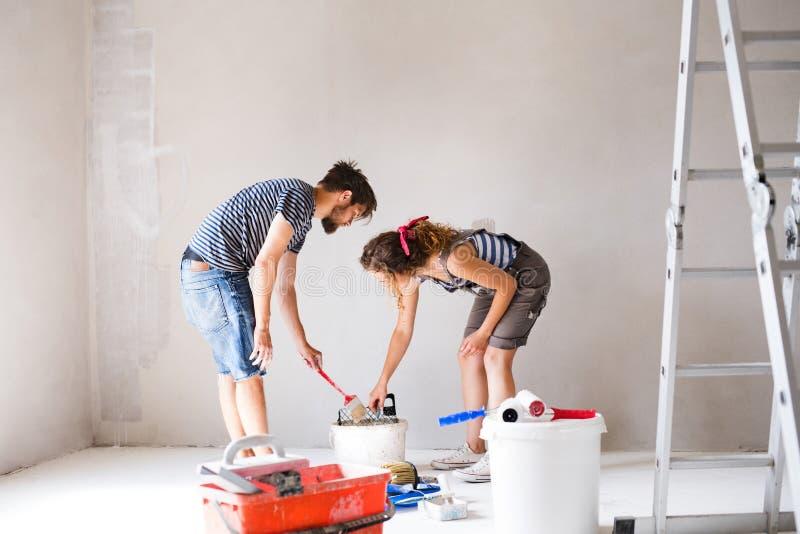 Paredes novas da pintura dos pares em sua casa nova imagens de stock