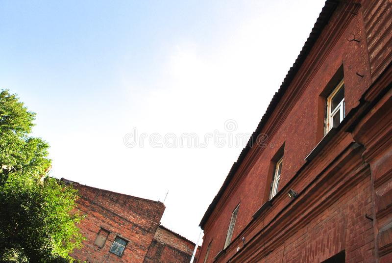 Paredes velhas da construção de tijolo vermelho com janelas, árvores verdes, vista da terra no telhado de ardósia, céu azul imagem de stock