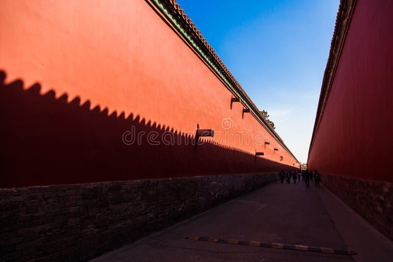 Paredes vermelhas com as telhas amarelas na parte superior em cada lado de uma estrada na Cidade Proibida, Pequim fotos de stock royalty free