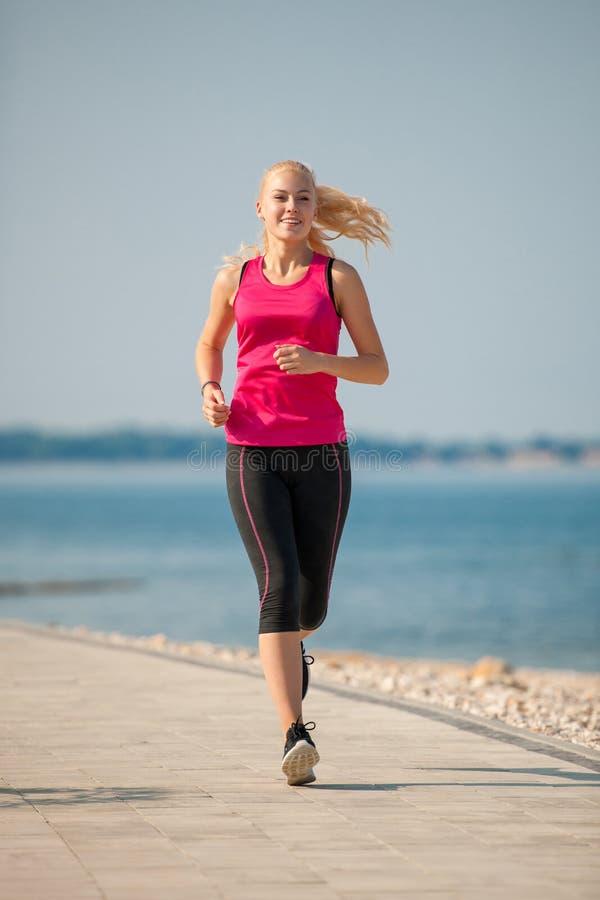 Pareggiando in spiaggia del Th - i runns della donna si avvicinano al mare sul morni dell'inizio dell'estate immagine stock