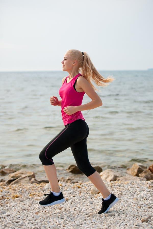 Pareggiando in spiaggia del Th - i runns della donna si avvicinano al mare sul morni dell'inizio dell'estate immagine stock libera da diritti