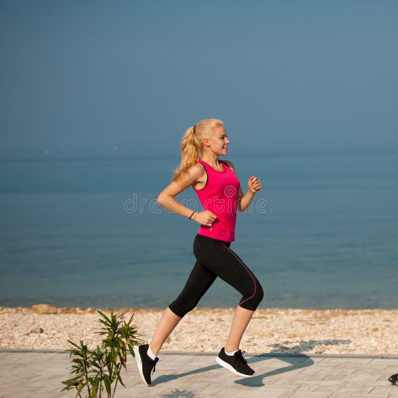 Pareggiando in spiaggia del Th - i runns della donna si avvicinano al mare sul morni dell'inizio dell'estate immagini stock libere da diritti