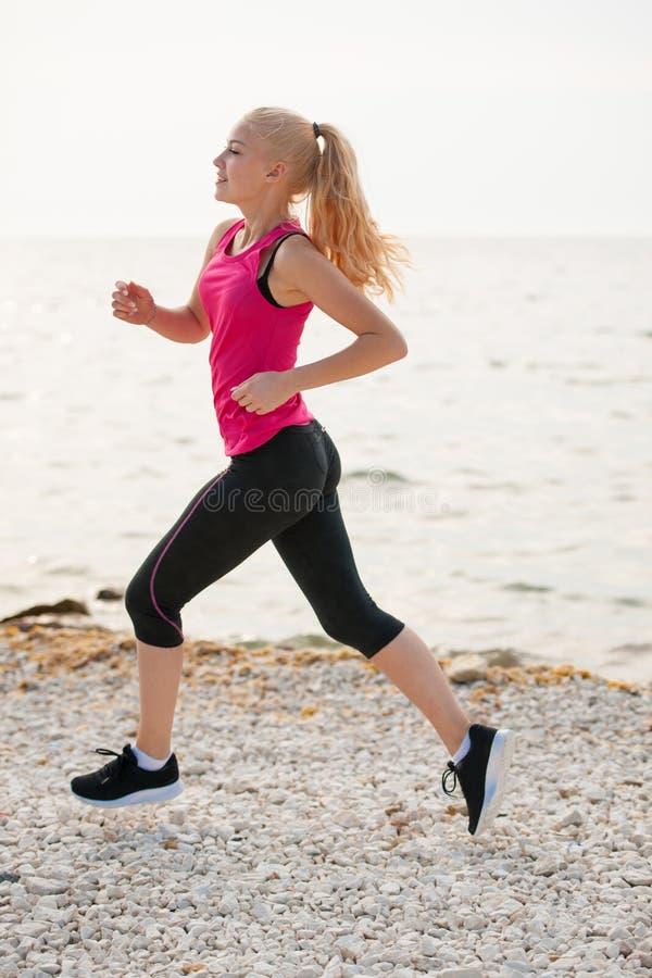 Pareggiando in spiaggia del Th - i runns della donna si avvicinano al mare sul morni dell'inizio dell'estate immagini stock