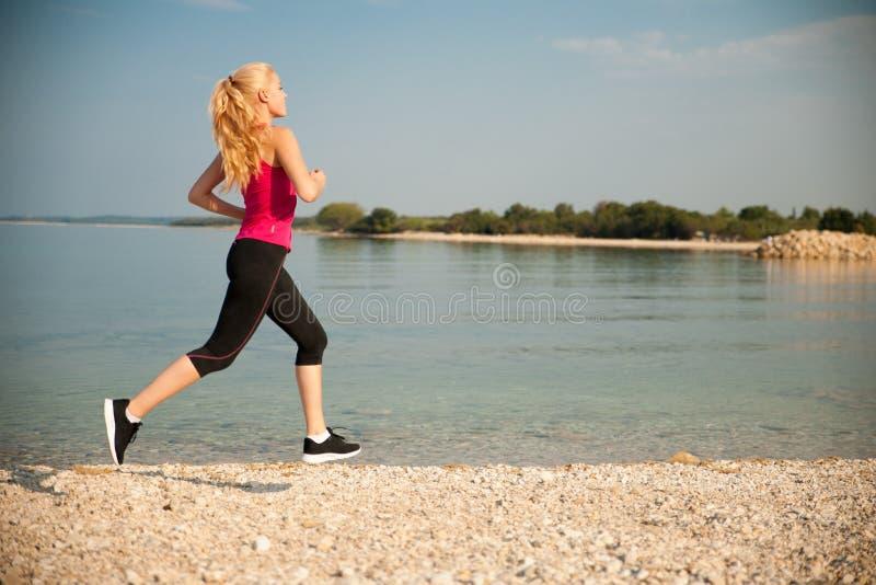 Pareggiando in spiaggia del Th - i runns della donna si avvicinano al mare sul morni dell'inizio dell'estate fotografia stock libera da diritti
