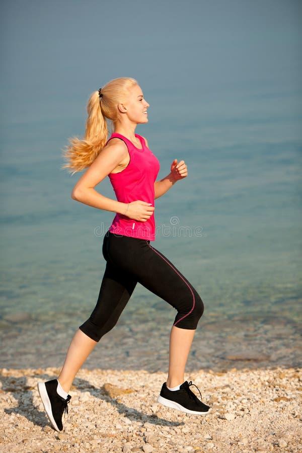 Pareggiando in spiaggia del Th - i runns della donna si avvicinano al mare sul morni dell'inizio dell'estate fotografie stock
