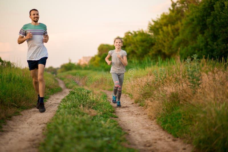 Pareggiare della figlia e del padre Funzionamento allegro della figlia e del padre in parco insieme fotografie stock