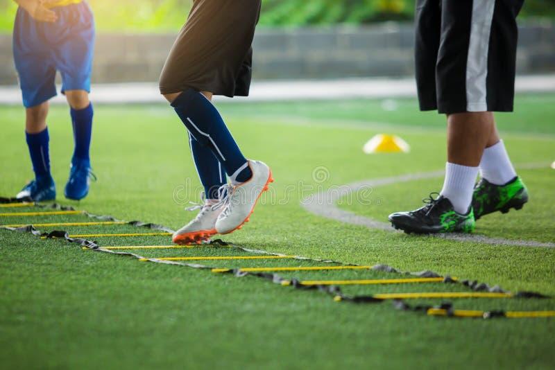 Pareggiare e salto del calciatore del bambino fra l'indicatore per addestramento di calcio La scala perfora gli esercizi per la s fotografie stock