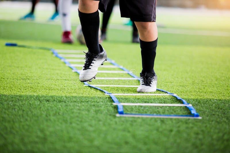 Pareggiare e salto del calciatore fra l'indicatore per addestramento di calcio con confuso altri giocatori che aspettano per segu fotografie stock