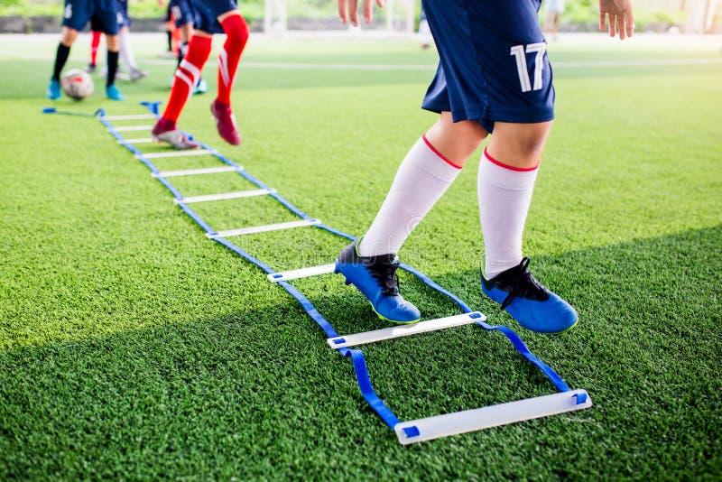 Pareggiare e salto del calciatore fra l'indicatore per addestramento di calcio con confuso altri giocatori che aspettano per segu fotografia stock