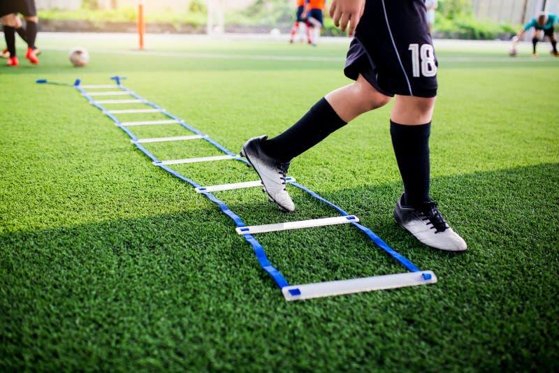 Pareggiare e salto del calciatore fra l'indicatore per addestramento di calcio con confuso altri giocatori che aspettano per segu immagini stock