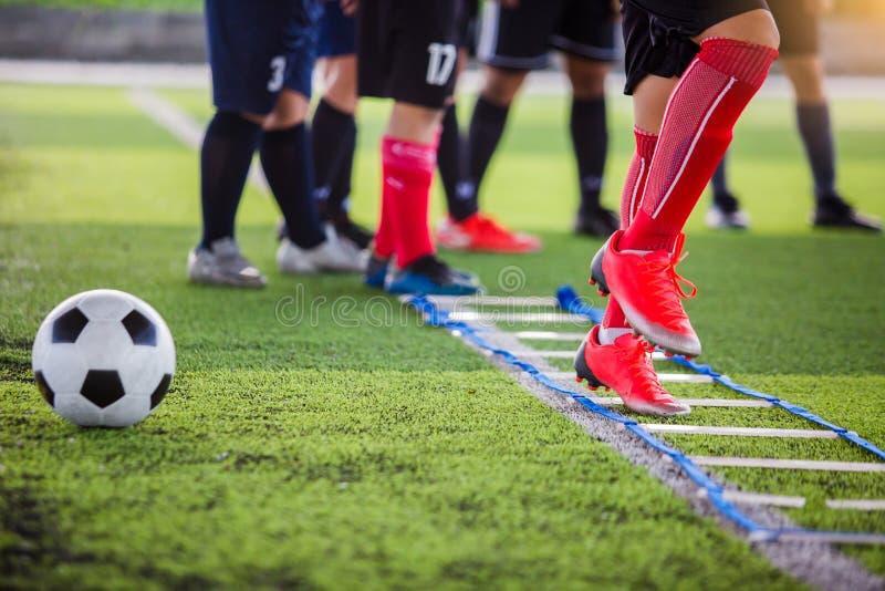 Pareggiare e salto del calciatore fra l'indicatore per addestramento di calcio La scala perfora gli esercizi per la squadra di ca fotografia stock libera da diritti