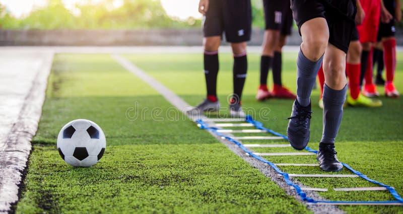 Pareggiare e salto del calciatore fra l'indicatore per addestramento di calcio La scala perfora gli esercizi per la squadra di ca fotografie stock libere da diritti