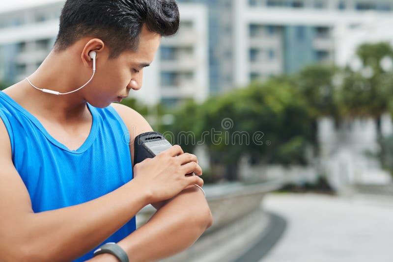 Pareggiatore asiatico con il bracciale di sport immagini stock