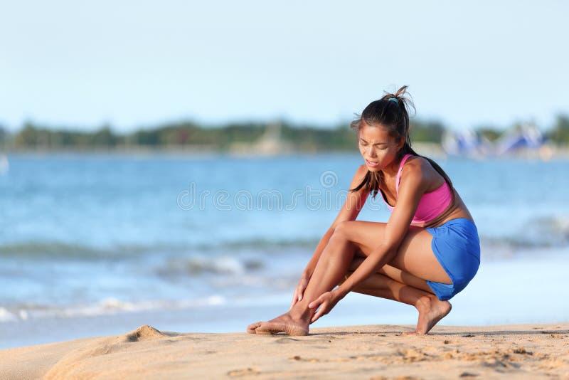 Pareggiatore che soffre dal dolore della caviglia su funzionamento della spiaggia fotografie stock libere da diritti