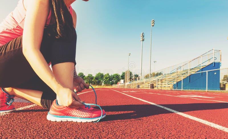 Pareggiatore femminile che lega le sue scarpe su una pista dello stadio immagine stock libera da diritti