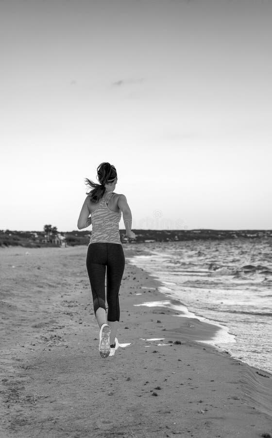 Pareggiatore sano della donna sulla spiaggia nel funzionamento di sera fotografie stock