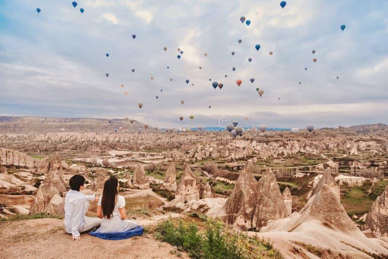 Pareja asiática viendo coloridos globos de aire caliente volando sobre el valle en Cappadocia, Turquía Esta época romántica de imagenes de archivo