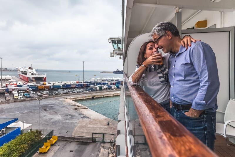 Pareja bebiendo una copa en la cubierta de un crucero fotografía de archivo