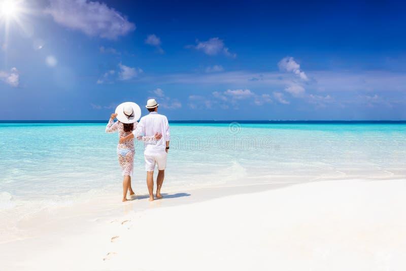 Pareja camina abrazándose en una playa tropical durante sus vacaciones fotografía de archivo