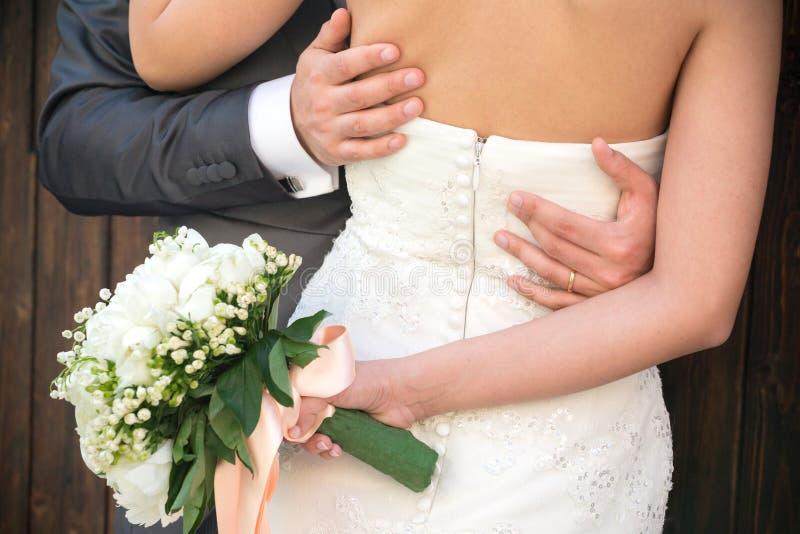 Pareja casada abrazada, detalle del busto y brazos foto de archivo