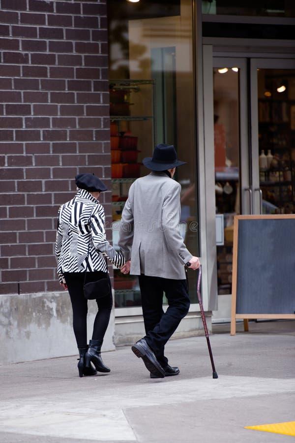 Pareja casada elegante cariñosa madura que da un paseo a lo largo de la calle fotos de archivo