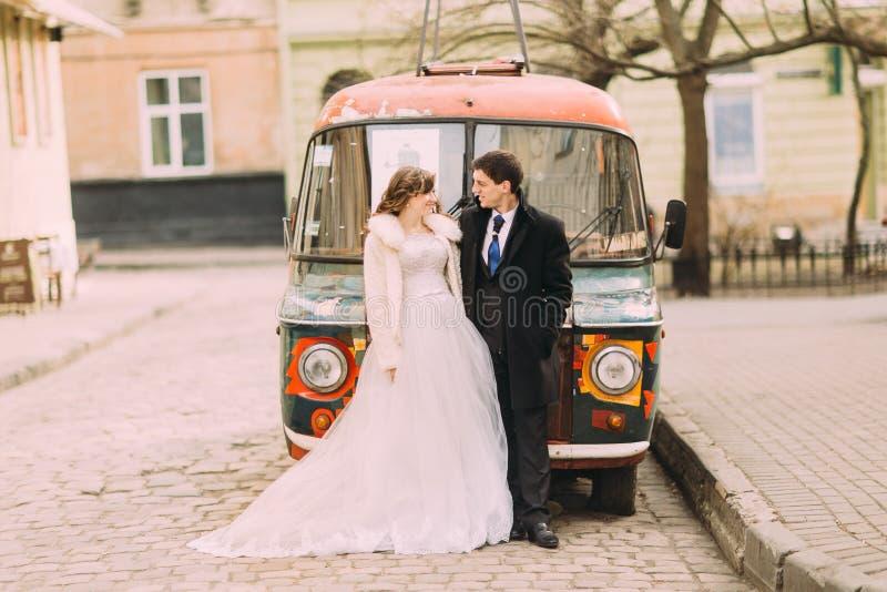 Pareja casada feliz empracing cerca del coche retro colorido imágenes de archivo libres de regalías